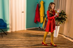 красивая ретро введенная в моду женщина в красном платье моча в горшке завод с небольшой моча консервной банкой стоковая фотография