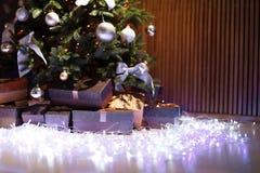 Красивая рождественская елка, fairy света и подарочные коробки Стоковые Фотографии RF