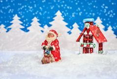 Красивая рождественская открытка с Сантой и дом в лесе зимы в снеге Стоковые Изображения