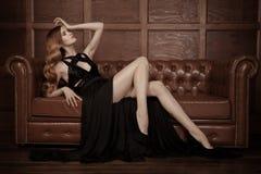 Красивая роскошная женщина сидя на кожаное VI Стоковые Фото