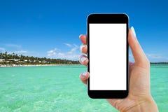 Красивая рука ` s женщины используя умный телефон на пляже tropicL около океана Экран изолированный Smartphone белый Пустой пусто Стоковое Изображение