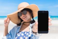 Красивая рука ` s женщины используя умный телефон на пляже Стоковая Фотография RF