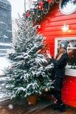 Красивая русская девушка во дне облака в одеждах зимы имея потеху в квадрате Tverskaya во времени рождества стоковое изображение rf