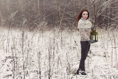 Красивая рыжеволосая девушка в mittens идя с лампой в фантастичном лесе зимы стоковая фотография rf