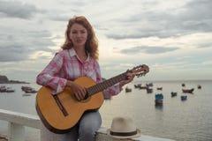 Красивая рыжеволосая девушка с гитарой Стоковая Фотография