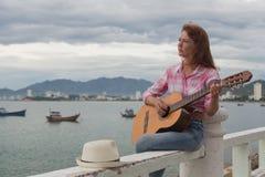 Красивая рыжеволосая девушка с гитарой Стоковые Изображения RF