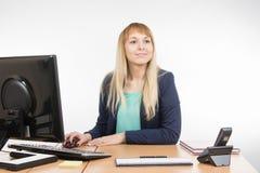 Красивая секретарша девушки работая на компьютере посмотрела посетителя Стоковые Фото