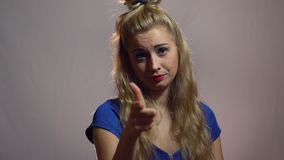 Красивая сексуальная белокурая девушка в голубом платье пункт на вас в студии с светлой предпосылкой Видео мотивировки акции видеоматериалы