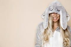 Красивая сексуальная белокурая женщина нося пижаму, костюм зайчика, усмехаясь счастливо Фотомодель в плюшке пасхи стоковое фото rf