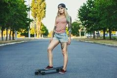 красивая, сексуальная блондинка битника с голубыми волосами в татуировке стоит с longboard стоковое фото