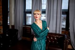 Красивая сексуальная блондинка женщины в элегантном зеленом сверкная платье Фотомодель при длинные ноги представляя в темном инте Стоковое Изображение
