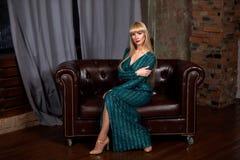Красивая сексуальная блондинка женщины в элегантном зеленом сверкная платье Фотомодель при длинные ноги представляя в темном инте Стоковые Фото
