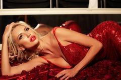 Красивая сексуальная женщина с светлыми волосами в роскошном красном платье Стоковое Фото