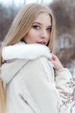 Красивая сексуальная белокурая девушка с длинными волосами, полными губами в белом пальто идя в древесины зимы Стоковые Фото