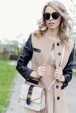 Красивая сексуальная девушка с скручиваемостями в солнечных очках и пальто идет улицы города на день весны яркий стоковая фотография