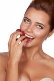 Красивая сексуальная женщина брюнет держа 4 ягоды на ее пальцах, сексуальный усмехаться и идет съесть поленики на белом backgro Стоковые Изображения RF