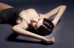 Красивая сексуальная женщина в женское бельё лежа на поле Стоковое фото RF