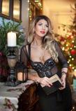 Красивая сексуальная женщина в элегантном черном платье с деревом Xmas в предпосылке Портрет модной белокурой девушки держа книгу Стоковое Изображение
