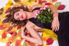 Красивая сексуальная женщина на листьях осени Стоковая Фотография