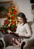 Красивая сексуальная женщина с деревом Xmas в чтении предпосылки книга сидя на стуле. Портрет женщины читая усаживание книги Стоковая Фотография