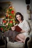 Красивая сексуальная женщина с деревом Xmas в чтении предпосылки книга сидя на стуле. Портрет женщины читая усаживание книги Стоковые Фотографии RF