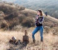 Красивая сексуальная усмехаясь женщина прерывая древесину с осью Стоковая Фотография