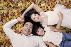 Красивая семья лежа на листьях осени Стоковое Изображение RF