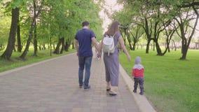 Красивая семья наслаждаясь летним днем в парке: маленький младенец уча как идти при мама и папа помогая ему сделать сток-видео