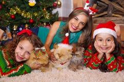 Красивая семья нося рождество одевает, обнимающ ее котов, курчавая девушка с красной связью в ее волосах пока Стоковая Фотография RF