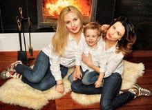 Красивая семья сидя на ковре меха на камине Стоковые Фото