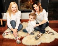 Красивая семья сидя на ковре меха около камина Стоковые Фотографии RF