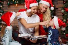 Красивая семья смеясь над с книгой Стоковое Изображение