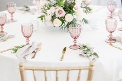 Красивая сервировка стола с посудой и цветками для партии, приема по случаю бракосочетания или другого праздничного события Стекл стоковое изображение