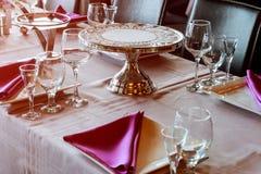 Красивая сервировка стола с посудой и цветками для партии, приема по случаю бракосочетания или другого праздничного события стоковое изображение