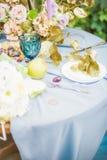 Красивая сервировка стола с посудой и цветками для партии, приема по случаю бракосочетания стоковая фотография