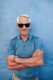 Красивая середина постарела мужчина представляя против голубой стены Стоковое фото RF