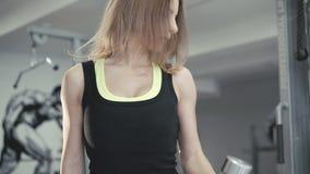 Красивая сильная девушка работает с гантелями в спортзале в 4K акции видеоматериалы