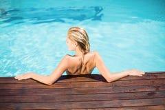 Красивая склонность женщины на деревянной палубе poolside Стоковое Изображение RF