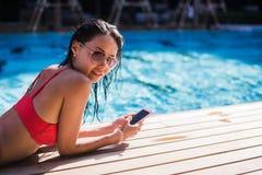 Красивая склонность женщины на poolside и печатать текстовое сообщение на мобильном телефоне Стоковая Фотография RF