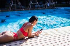 Красивая склонность женщины на poolside и печатать текстовое сообщение на мобильном телефоне Стоковое Фото