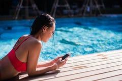 Красивая склонность женщины на poolside и печатать текстовое сообщение на мобильном телефоне Стоковое фото RF