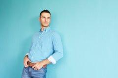 Красивая склонность человека против стены бирюзы Стоковая Фотография RF
