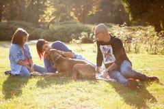 Красивая смеясь над семья из трех человек играя в парке с thei Стоковая Фотография RF