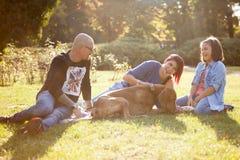 Красивая смеясь над семья из трех человек играя в парке с thei Стоковые Фото