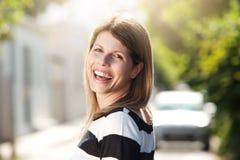 Красивая смеясь над женщина стоя outdoors на улице Стоковые Изображения RF