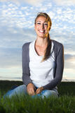 Красивая смеясь над молодая женщина сидя в поле Стоковое Изображение RF
