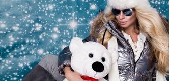 Красивая сногсшибательная женщина с длинными светлыми волосами и совершенной стороной одела в одежде зимы, куртке серебра теплых  Стоковые Изображения RF