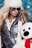 Красивая сногсшибательная женщина с длинными светлыми волосами и совершенной стороной одела в одежде зимы, куртке серебра теплых  Стоковое Изображение RF