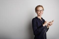 Красивая современная коммерсантка держа телефон mobil с белой стеной на предпосылке Стоковые Изображения