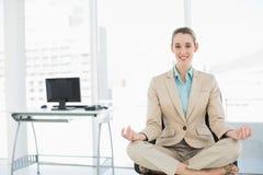 Красивая спокойная женщина сидя в положении лотоса на ее вращающееся кресло Стоковое фото RF